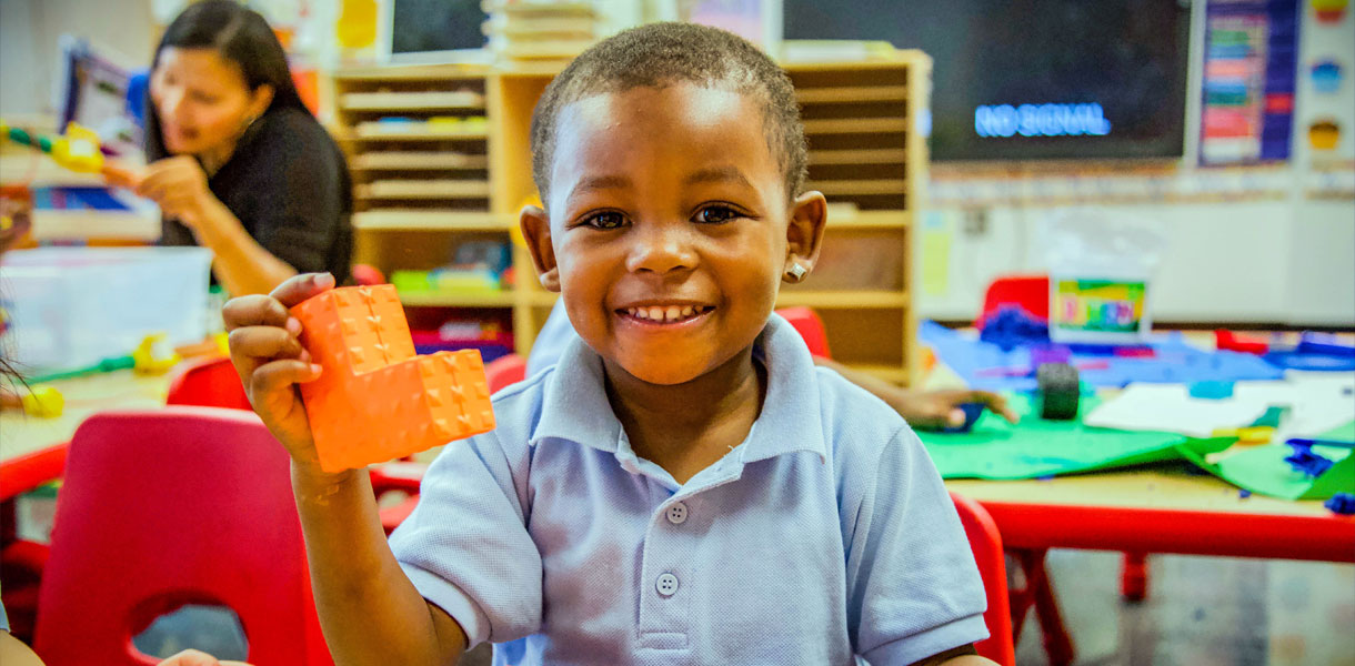 A 3-K student in the classroom smiles at the camera and holds an orange building block