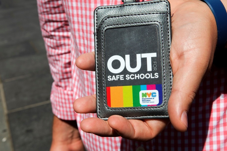 "A person holds out a wallet showing an ID card that reads ""Out for Safe Schools"""