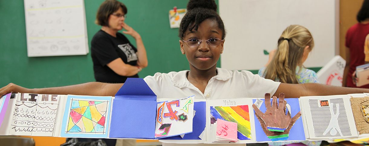 Young Student Holding Up Her Art Project in Class