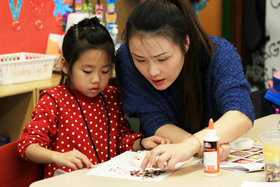 A woman helps a young student with an arts project, gluing colorful dots to a sheet of paper.