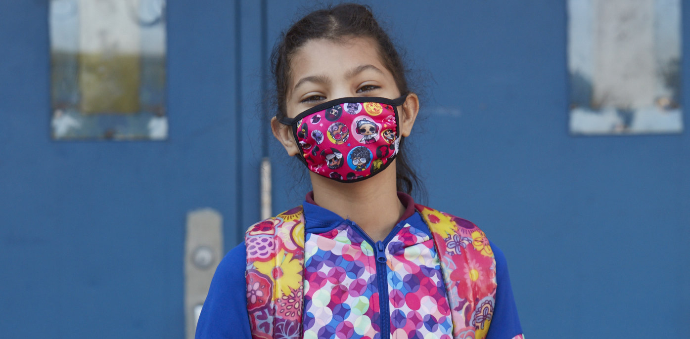 Smiling young girl with a mask on in front of a school