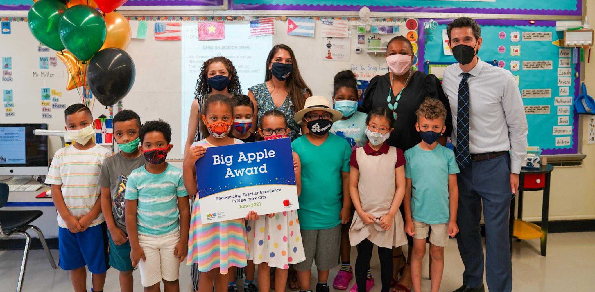 Class standing with teacher celebrating winning the Big Apple Award