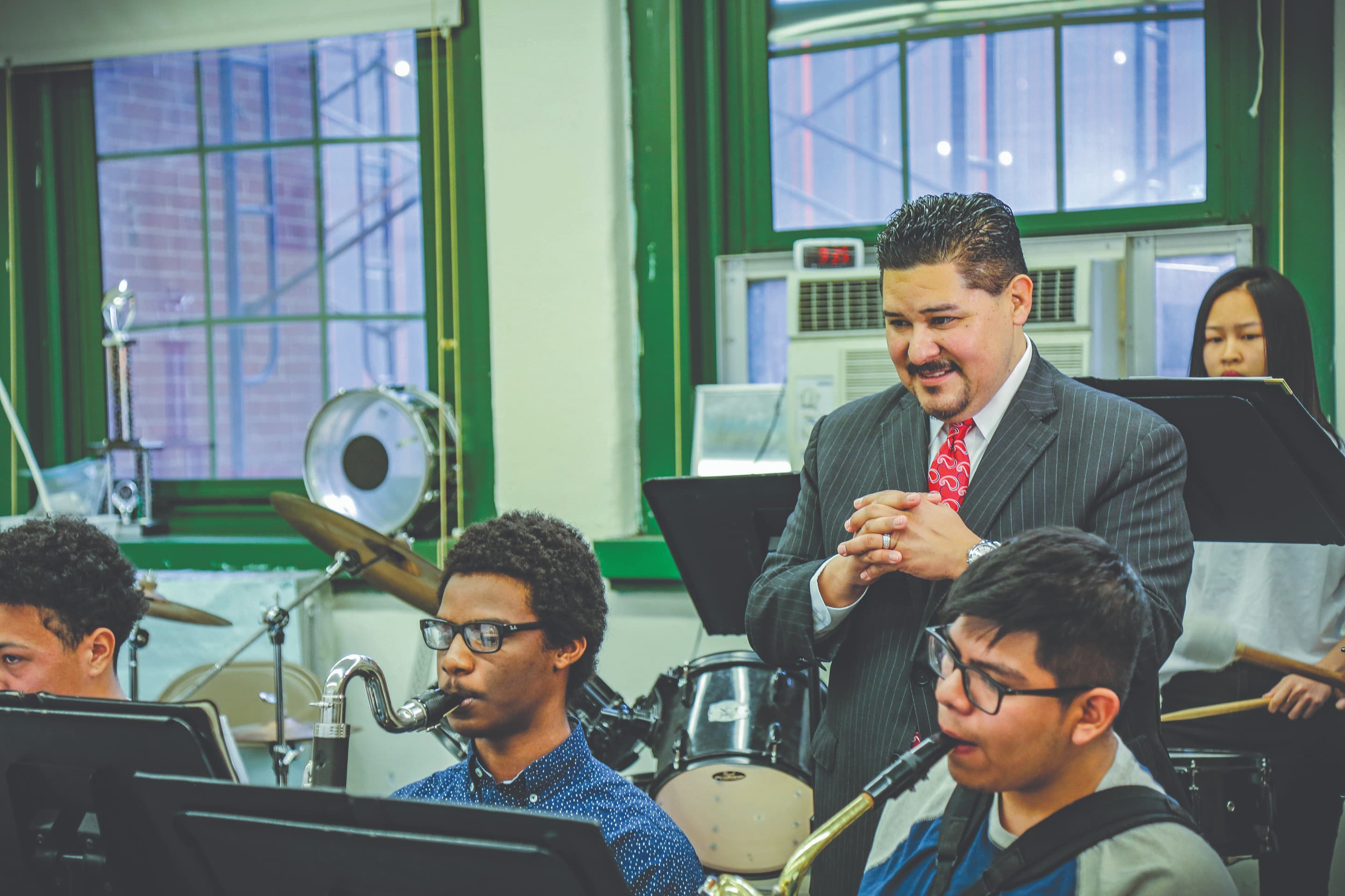 Chancellor Carranza listening to band students play in classroom