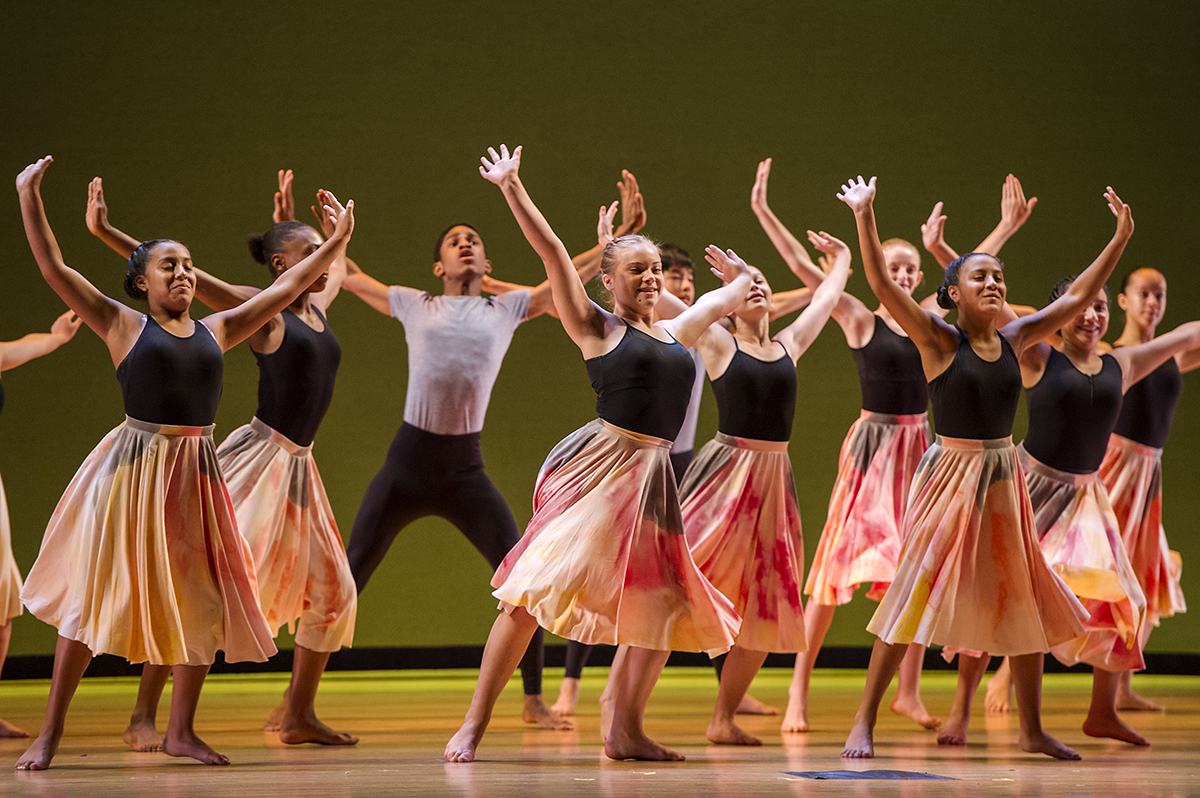 A photo of student dancers posing with their hands extended upwards at SAI Finale