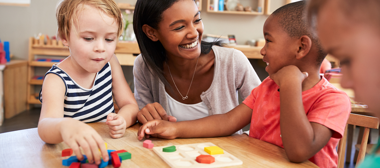 Preschool children and their teacher build with blocks in their classroom.