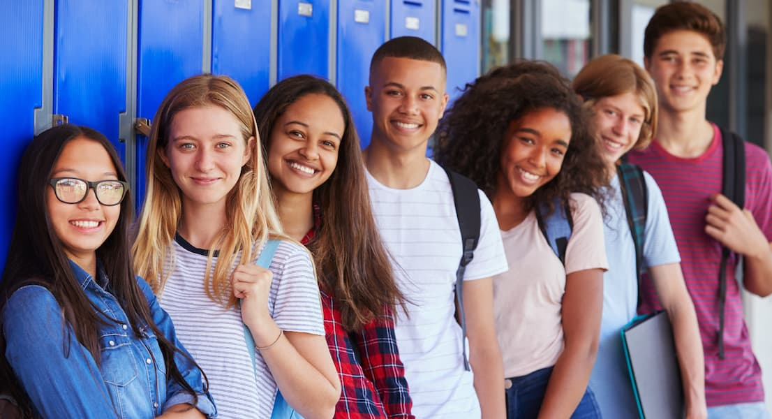 Ninth grade students lean against lockers in a hallway, smiling for the camera. They are excited for high school, wearing backpacks.