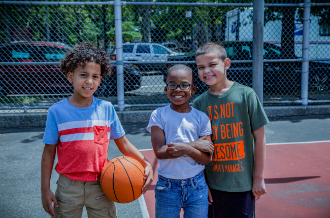 Three kids stand on a basketball court during summer