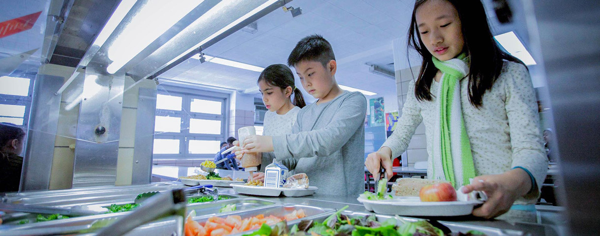 Students help themselves to salad as part of a healthy lunch at school