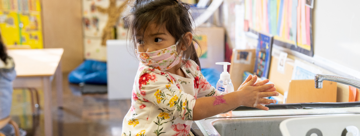 Young girl with a mask on washing her hands in a classroom