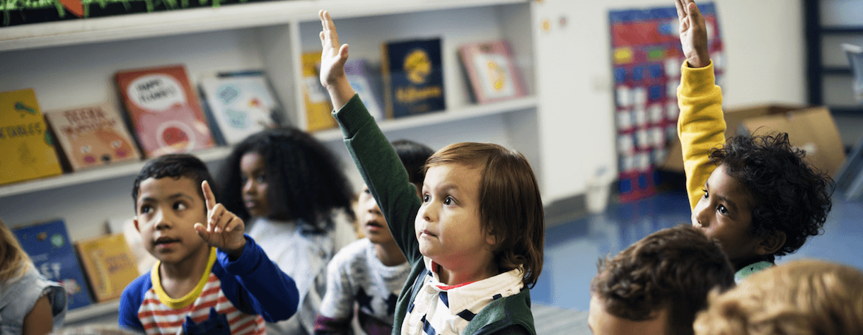 Kindergarten students in class, raising their hands