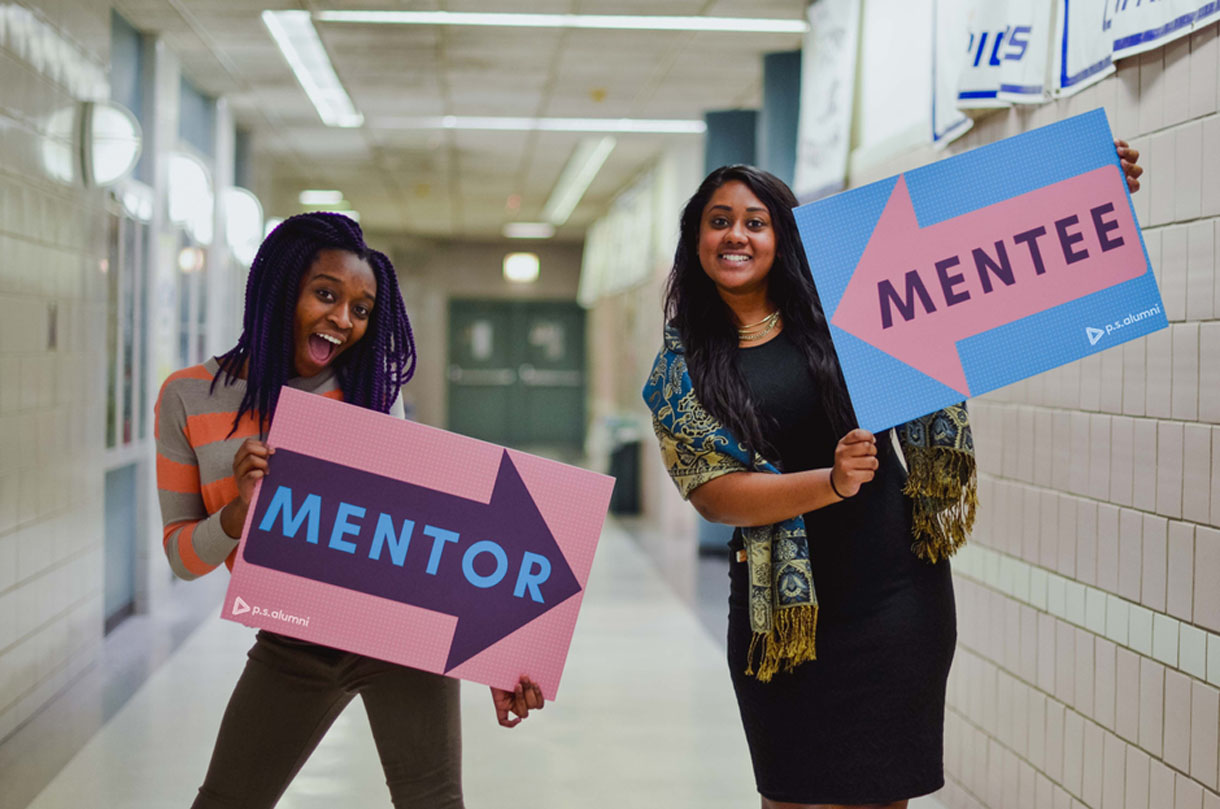 p.s. alumni mentor and mentee with signs pointing at each other