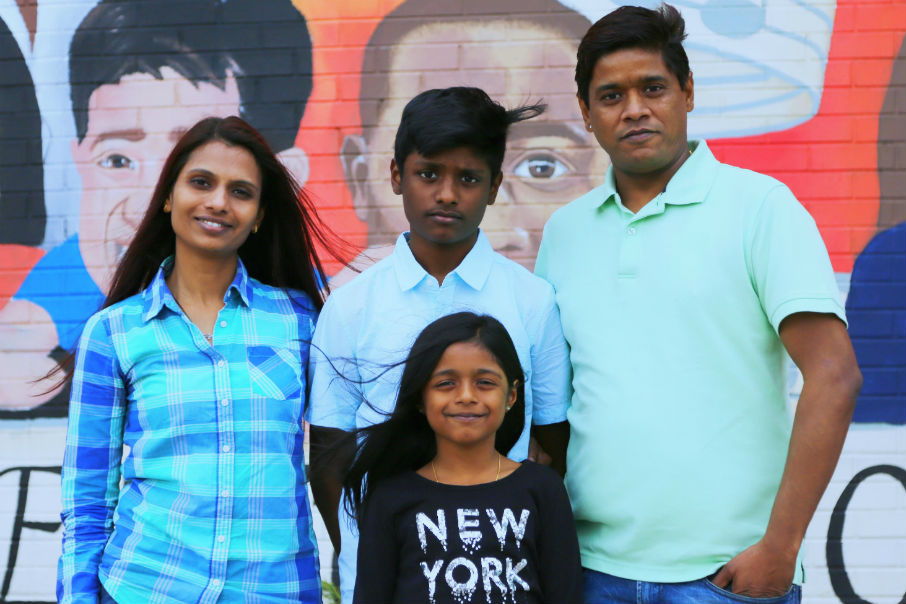 Two parents stand with their children in front of a colorful mural.