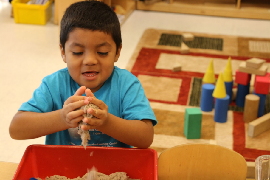 A child plays with sand at sand box area for center time.