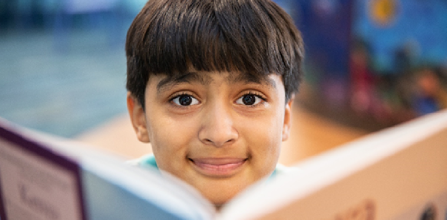 Image of a smiling boy behind a book