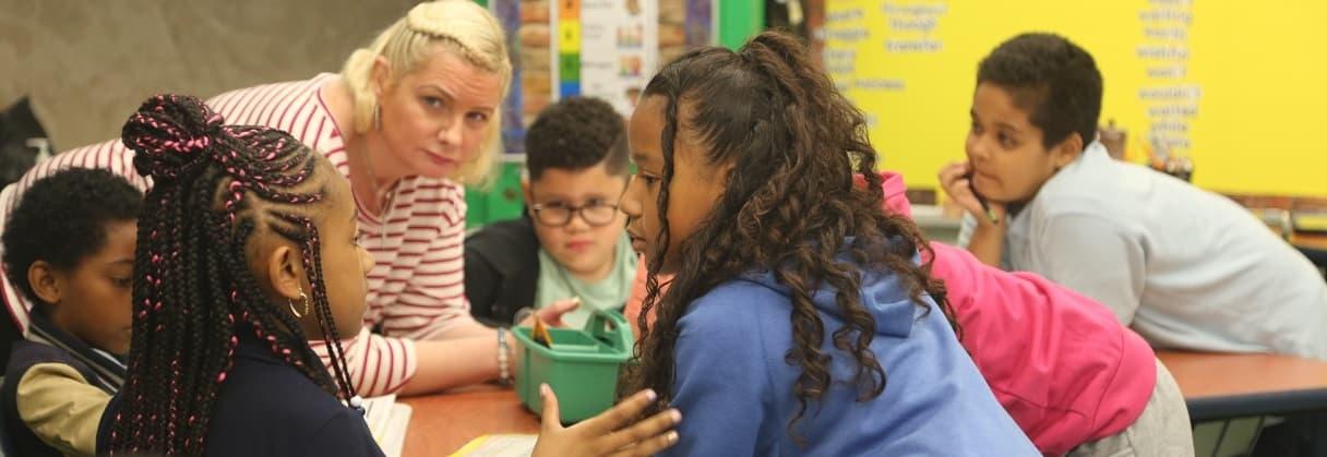 children and a teacher talking