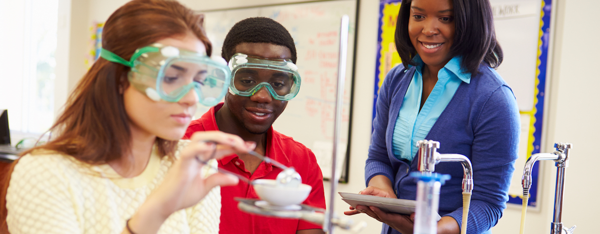 Two high school students work on a science experiment together in class while their teacher watches, smiling