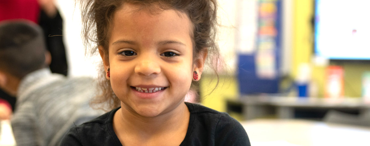 In her classroom, a young Latina student wears ladybug earrings and smiles at the camera
