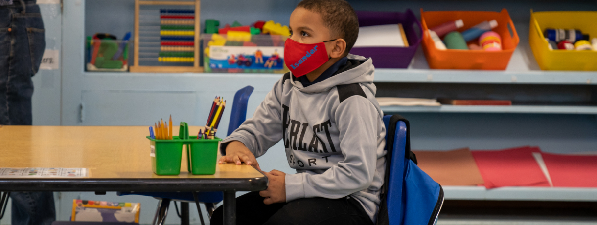 Young boy with mask in a classroom