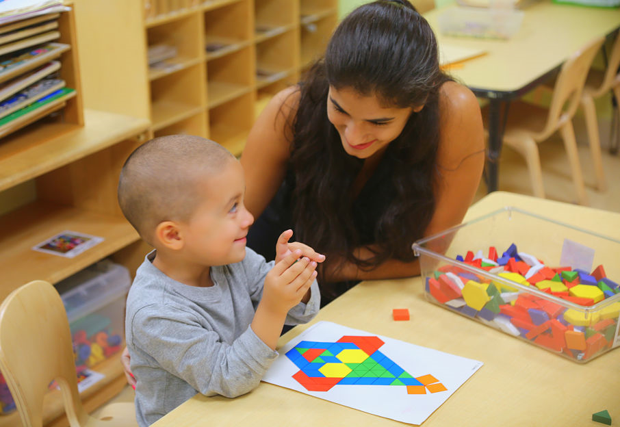 Teacher helps young child with shapes