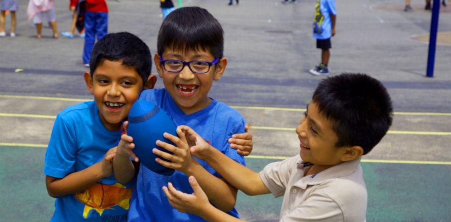 Three boys holding football on playground