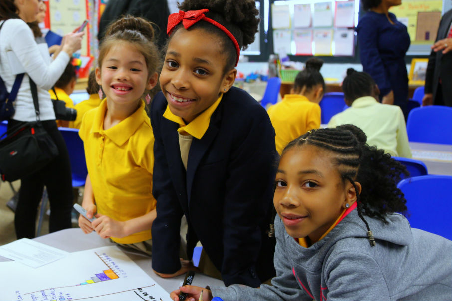 Three girls look up from a shared project to smile at the camera.