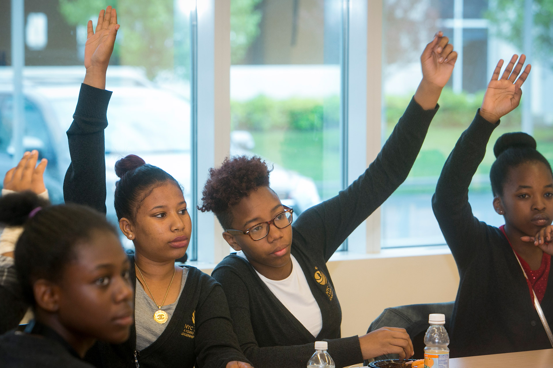 Two girls in class raising their hands
