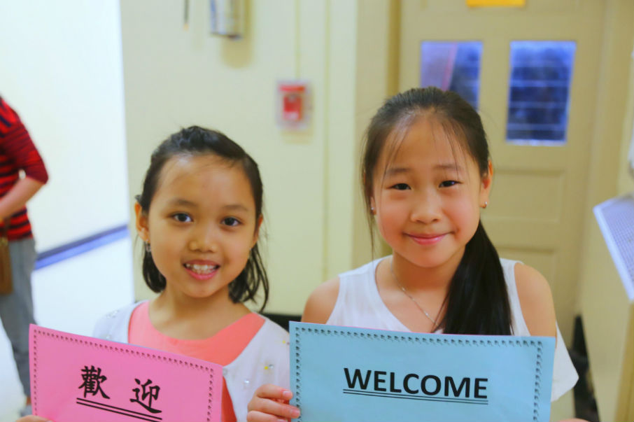 "Two girls hold up signs, in English and Chinese respectively, that say ""Welcome"""