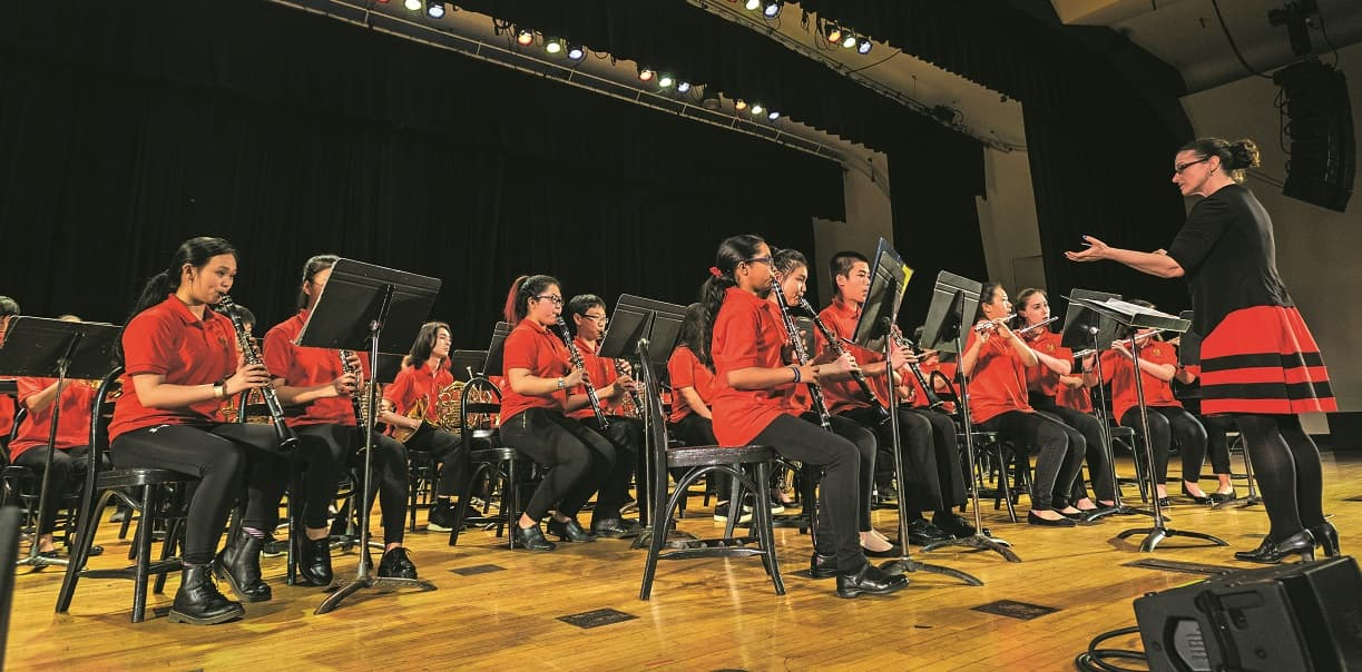 Students, all wearing red shirts, perform in an orchestra on stage with a woman conductor in a red skirt.