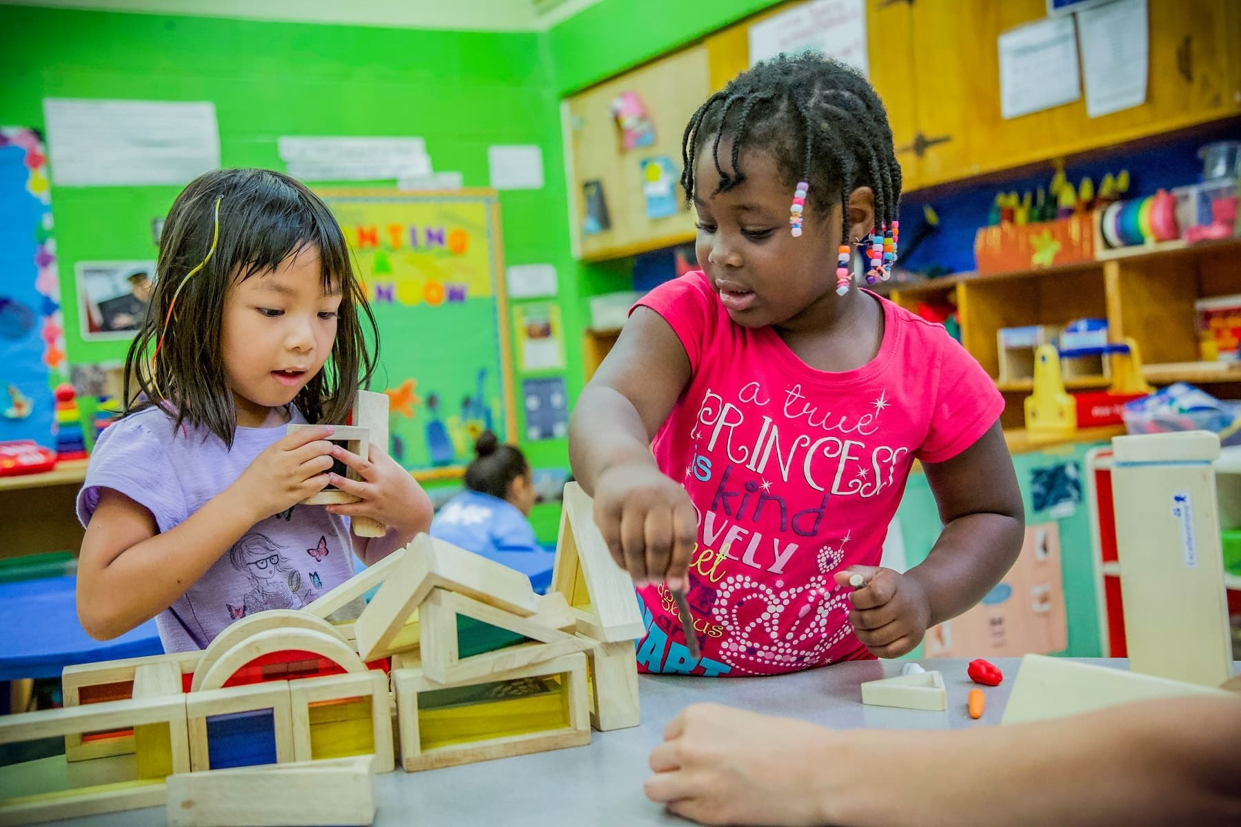 Young students play with blocks in a classroom.