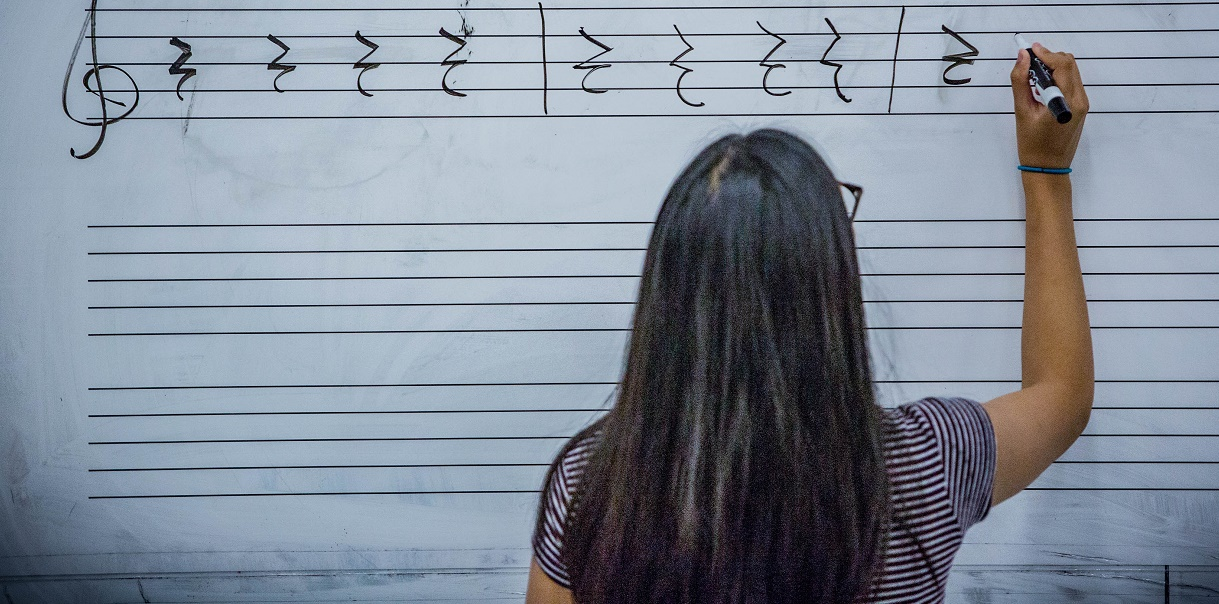 girl writing music at a whiteboard in class
