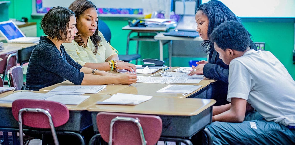 Parents, students and teachers meet and discuss student progress in the classroom
