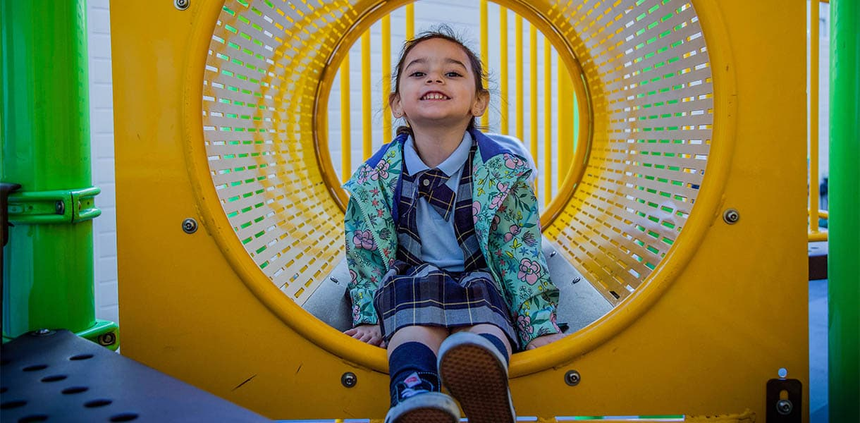 Girl sitting inside of play tunnel at a children's playground