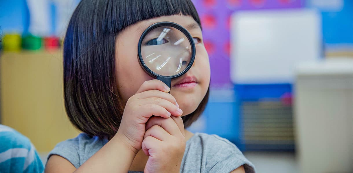Pre-K student holding a magnifying glass