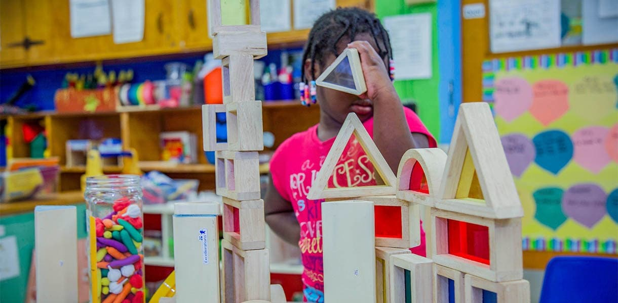 Young pre-k student plays with building blocks in classroom