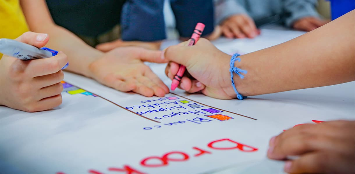 Childen's hands holding pen and crayons show them working together on a project in a classroom